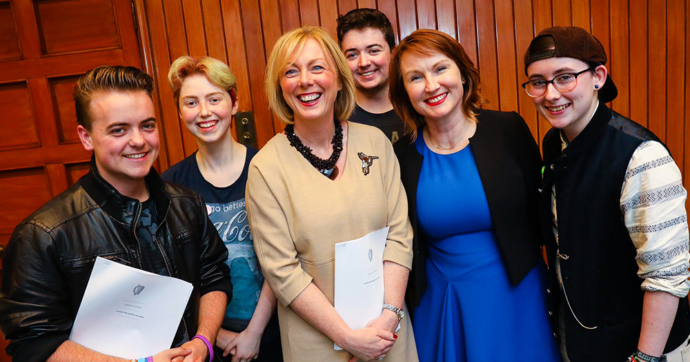 Gender Recognition Act is held by Regina Doherty who is in the centre of the photo. Moninne Griffith is also in the photo along with LGBT+ teenagers