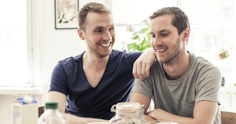 Two men sit in the kitchen smiling at each other.