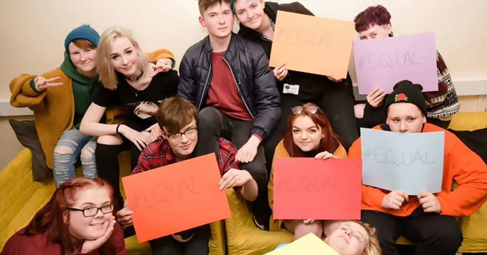 """northern ireland LGBT youth hold signs that read """"equal"""""""