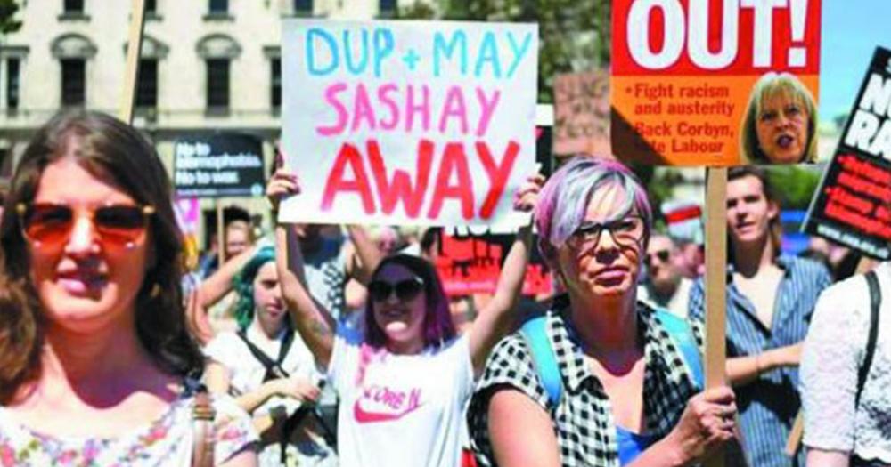 banner reads DUP and Theresa May sashay away