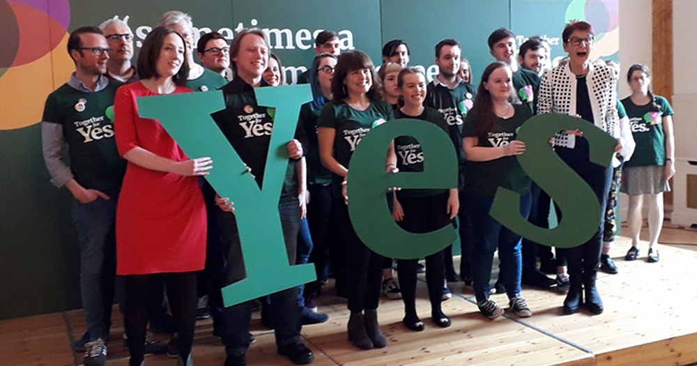 together for yes campaigners pose for a photo with giant YES