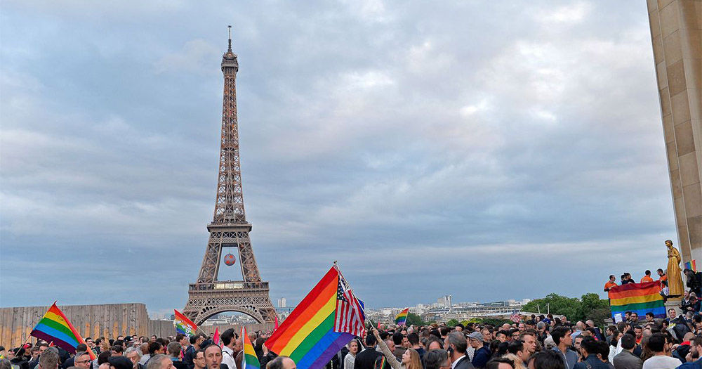 The Eiffel Tower and French parliament surrounding by crowds holding gay pride flags