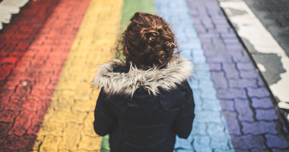Girl walks along a Pride rainbow footpath