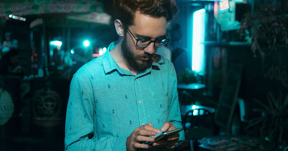 Grindr investigation: an in blue shirt looks down at his phone