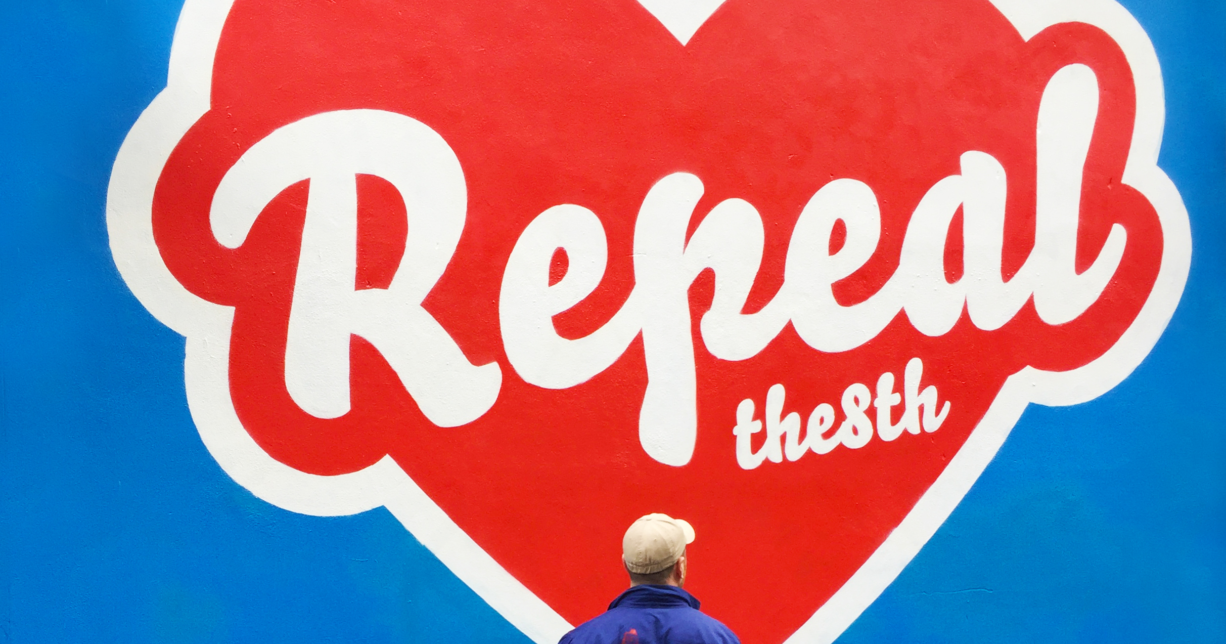 Artist Maser standing in front of the 'repeal the 8th' mural
