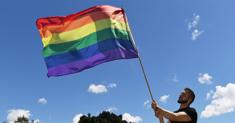 New Zealand man waves a pride flag against the sky as a backdrop