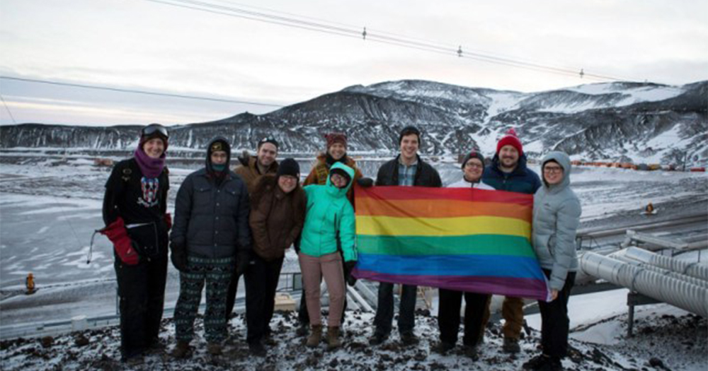A group of LGBT+ people in Antarctica holding the rainbow flag