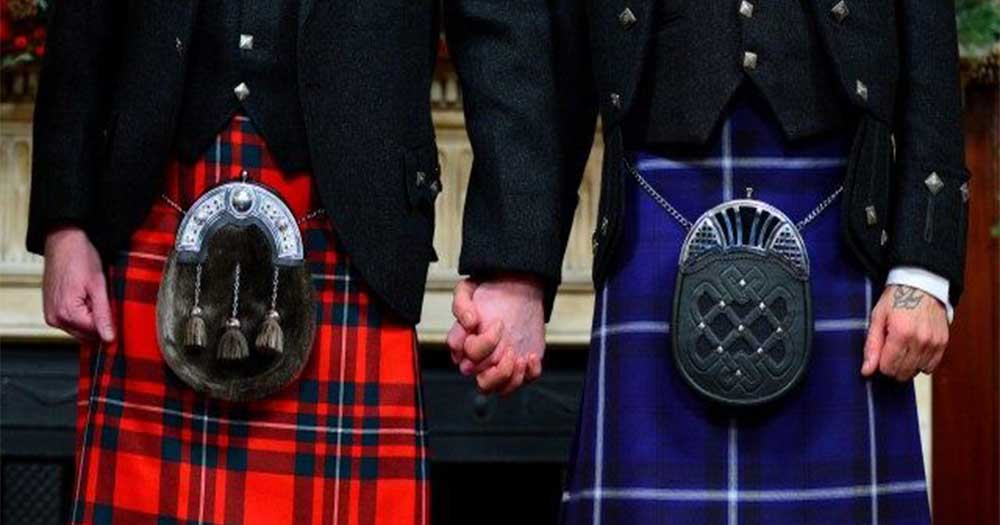 Close up of gay couple in kilts holding hands as ministers perform same-sex marriage