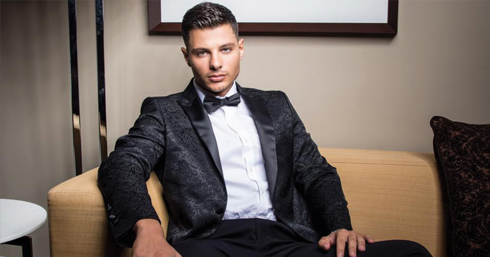 Jordan Bruno in a tuxedo sitting on a couch