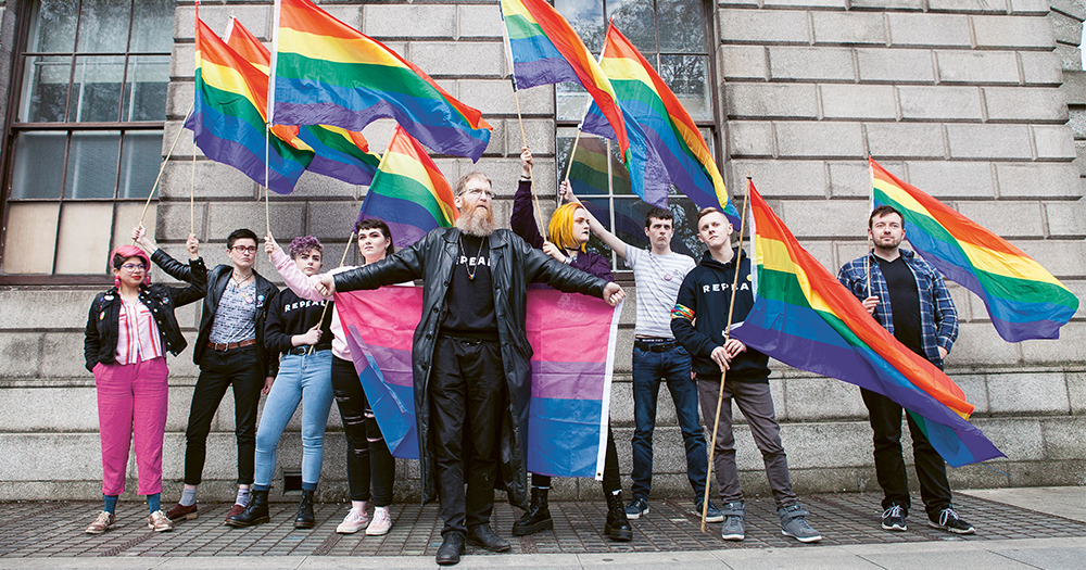 radical Queers stand with rainbow flags