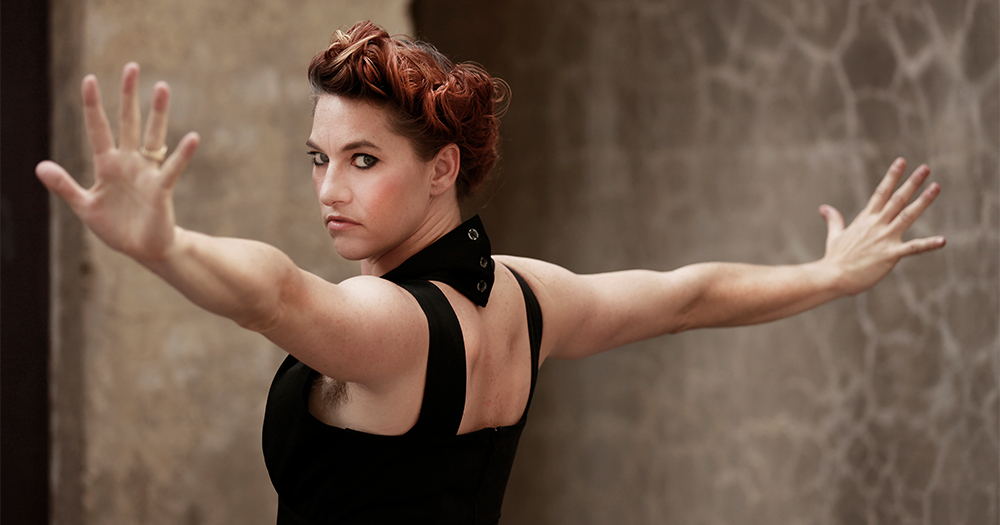 Amanda Palmer standing with arms outstretched looking over her shoulder toward the camera