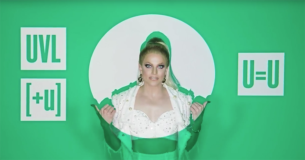 Drag queen Courtney Act standing against a green background