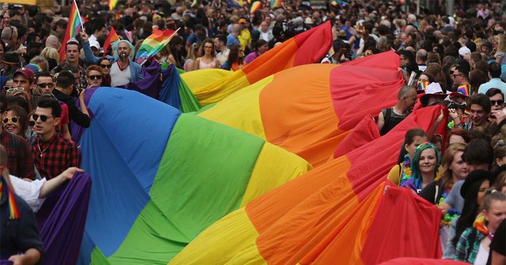 A parade of people carrying the pride flag