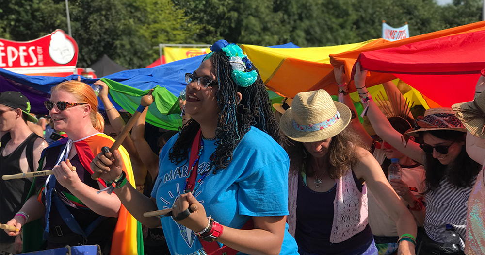 A group of young woman at Body&Soul playing instruments and carrying a rainbow flag