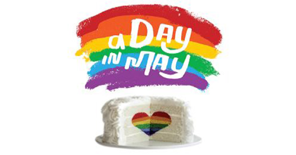 Poster for A Day In May at the Olympia Theatre depicting a white cake with a piece cut out and a rainbow coloured heart in the sponge
