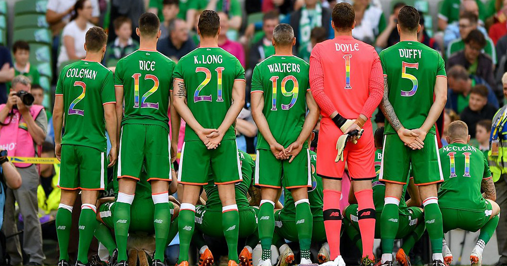 The Irish soccer team in a line viewed from behind with rainbow flag incorporated into their kit