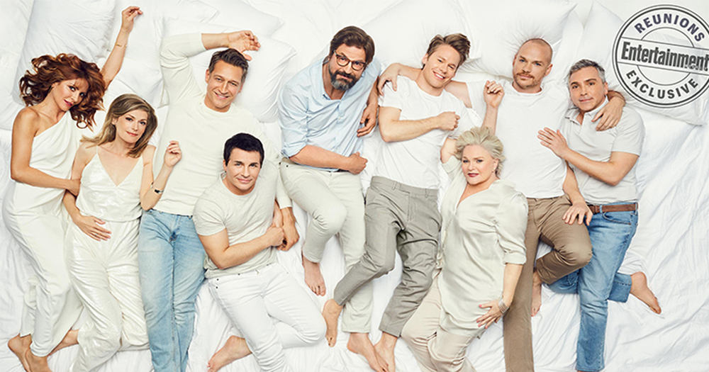 The cast of the US version of Queer As folk all dressed In white posing while lying across a gigantic bed