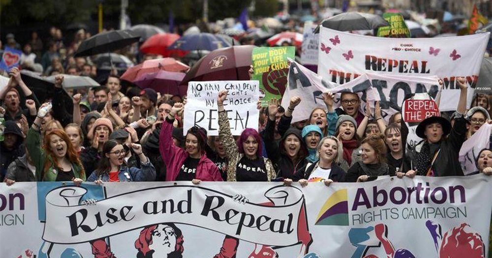 A group of women marching for change holding a sign saying 'Rise And Repeal'