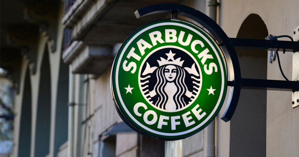A Starbucks sign hanging from the exterior of a store
