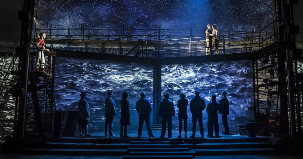 The cast of The Last Ship stand on stage against projections of the ocean