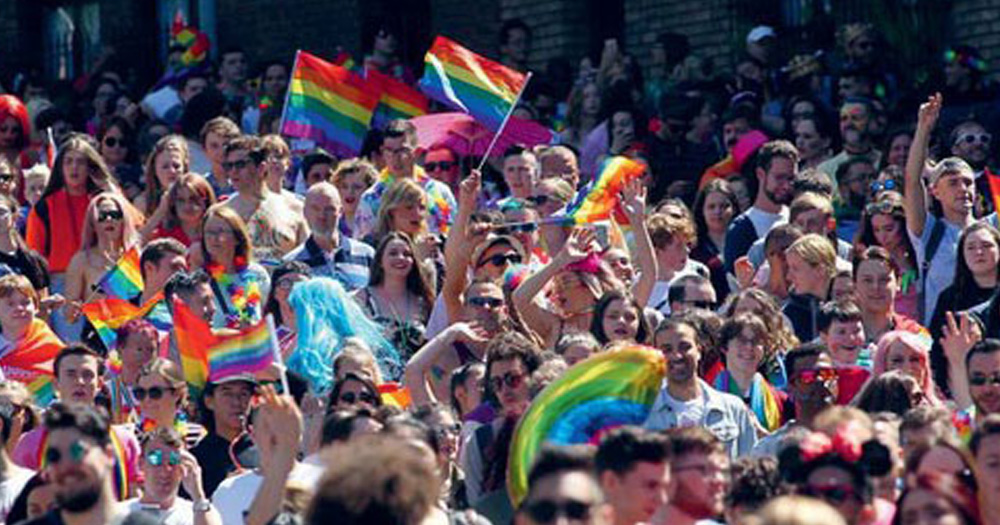 A crowd holds flags at Cork Pride