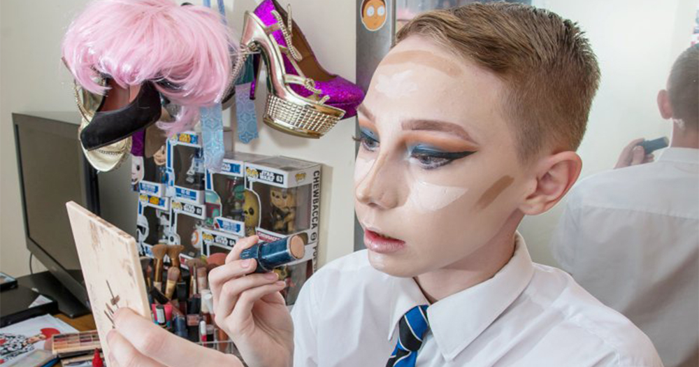 Lewis Bailey who was banned from his school show sits in his bedroom applying drag makeup