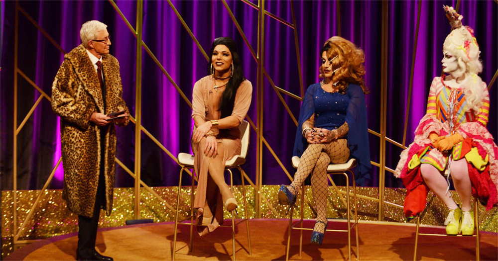 Paul O'Grady in a leopard skin coat on the set of Blind Date interviewing an all drag queen lineup of contestants