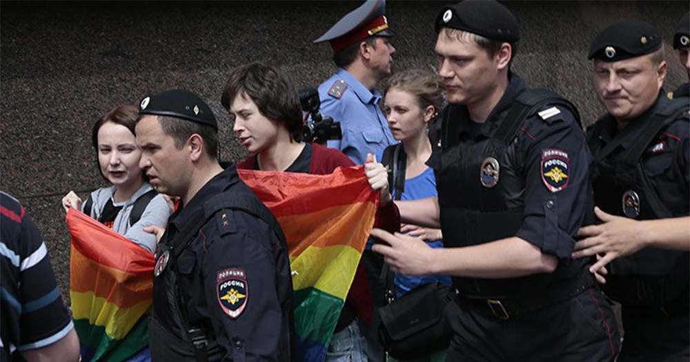 A group of young protestors holding a rainbow flag are bundled away by authorities in Chechnya