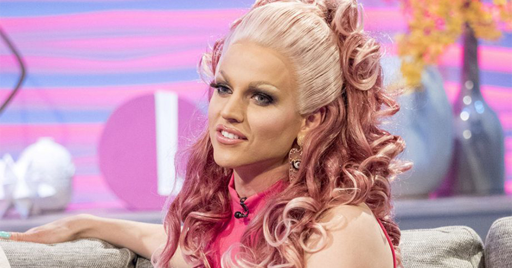 Courtney Act in drag sitting on a couch
