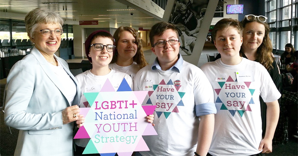 Katherine Zappone and Una Mulally with a group of young people holding a sign which reads LGBTI+ National Youth Strategy which inspired the report on the gender recognition act