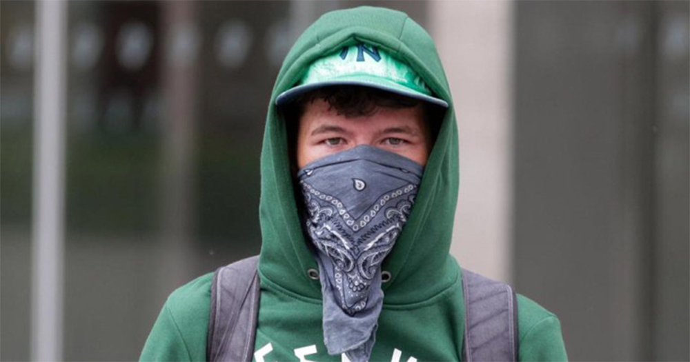 Eoin Berkely, the George vandal, with his hood up and lower face covered with a bandana