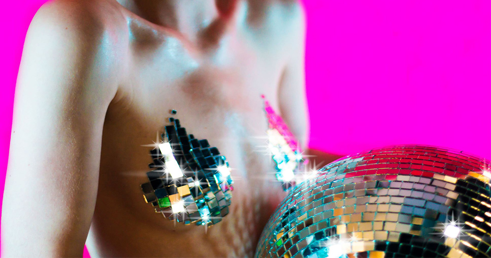 The glitter tits promotional poster showing a woman's naked upper body with tiny mirror tiles covering her breasts as she holds a disco ball