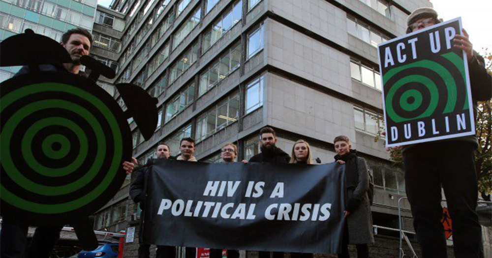 "ACT UP activists on a Dublin street outside government buildings holding signs saying ""HIV is a political crisis"""