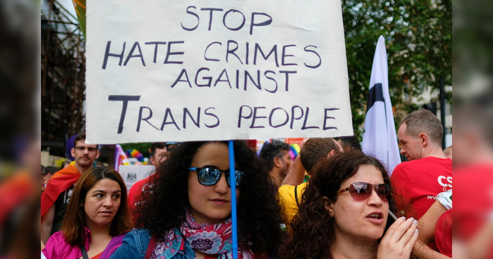 "in Ireland a women holds a sign whihc says ""stop hate crime against trans women"""