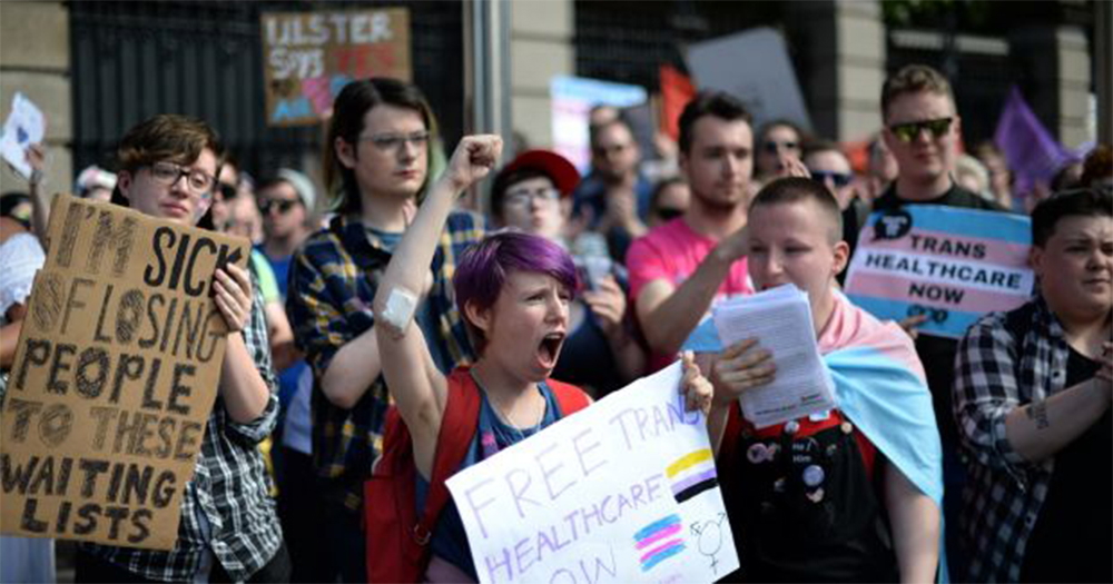 A group of young trans activists holding signs demanding better trans healthcare at a Trans Pride March