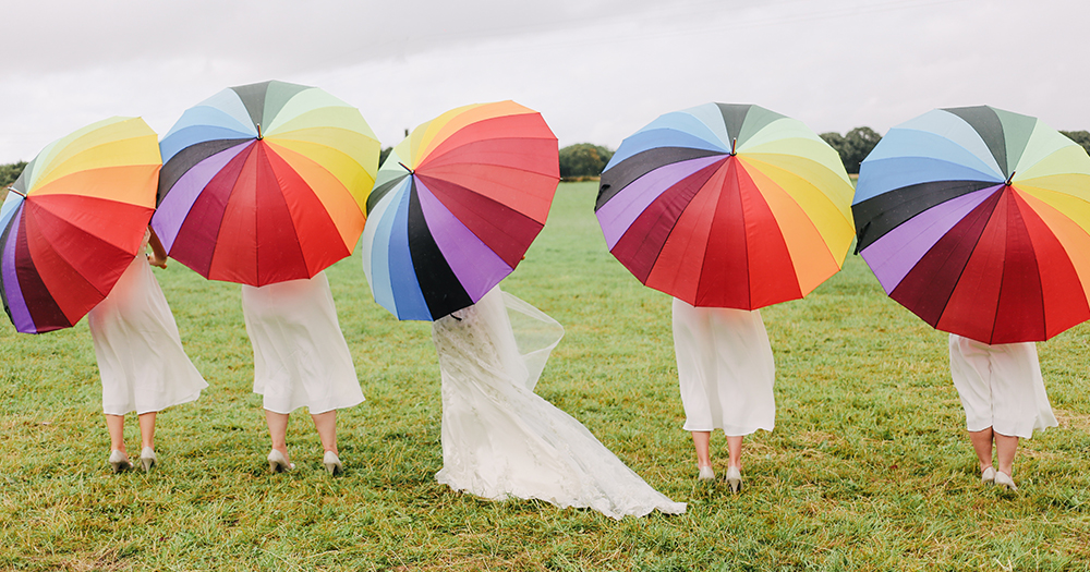 People in dresses hold rainbow umbrellas at a Marriage