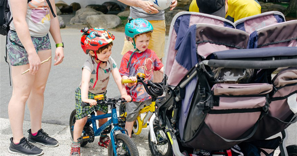 A pair of young theybies - gender neutral children, on their bikes wearing helmets looking into a pram as a man attends to the baby inside