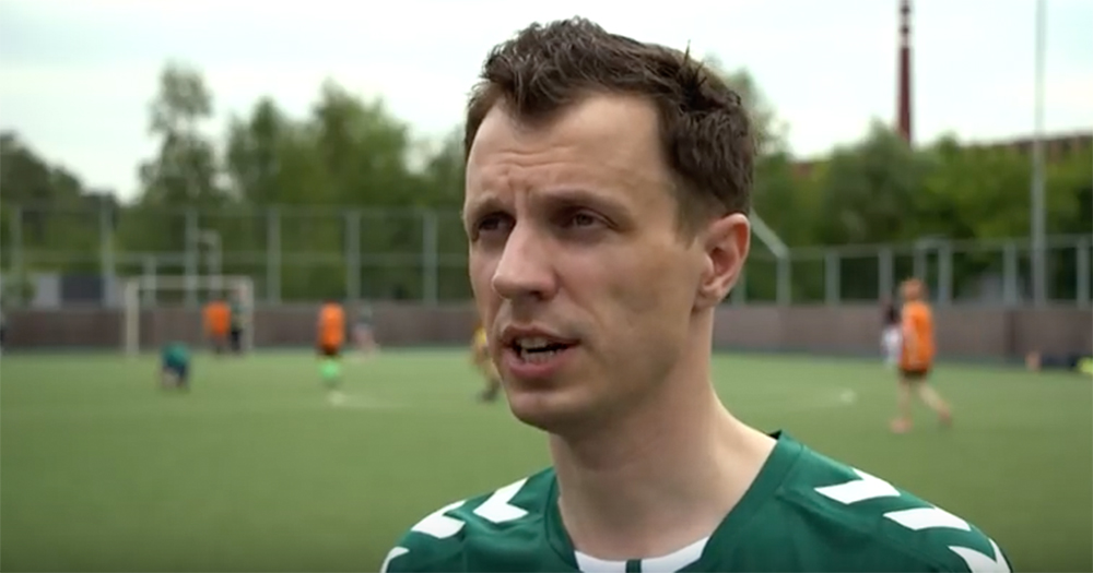 Aleksandr Agapov, the president of a group representing LGBT+ soccer fans, being interviewed on a football pitch