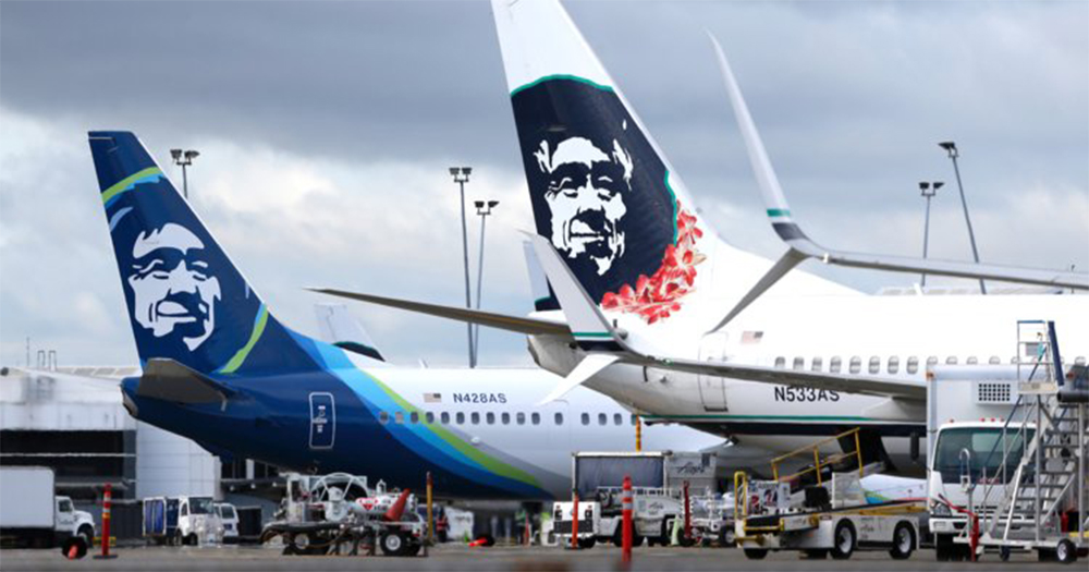 Two Alaska Airlines jets sit side by side on the runway, the sky behind them cloudy