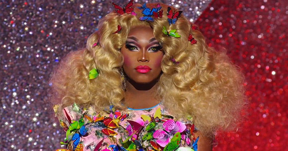 Drag queen Asia O'Hara faces the camera in a butterfly decorated dress with butterflies in her huge wig