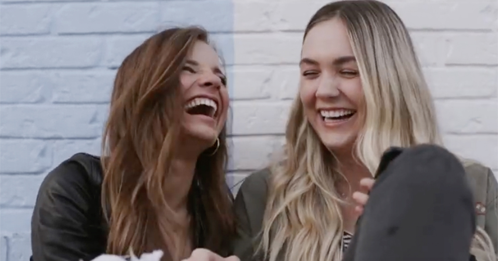 A still from the gay cure video featuring two teenage girls sitting and laughing against a brick wall
