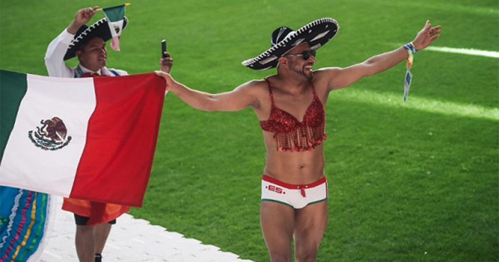 Two members of Team Mexico at the opening ceremony of the Gay Games, one man untraditional costume holding the country's flag, the other man in a sombrero, underwear and a woman's glittery bra