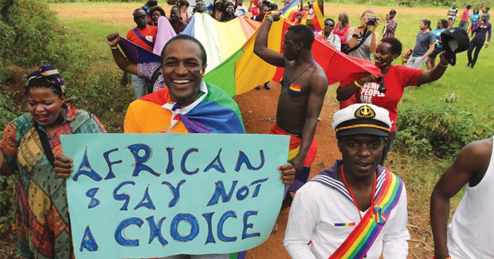 A group of pro-gay marchers in Ghana, dressed in bright clothing holding signs and rainbow flags