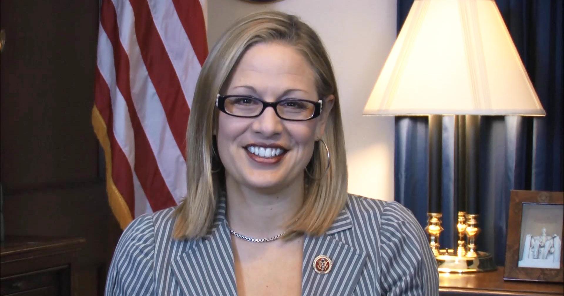 Krysten Sinema smiles at camera in her office.