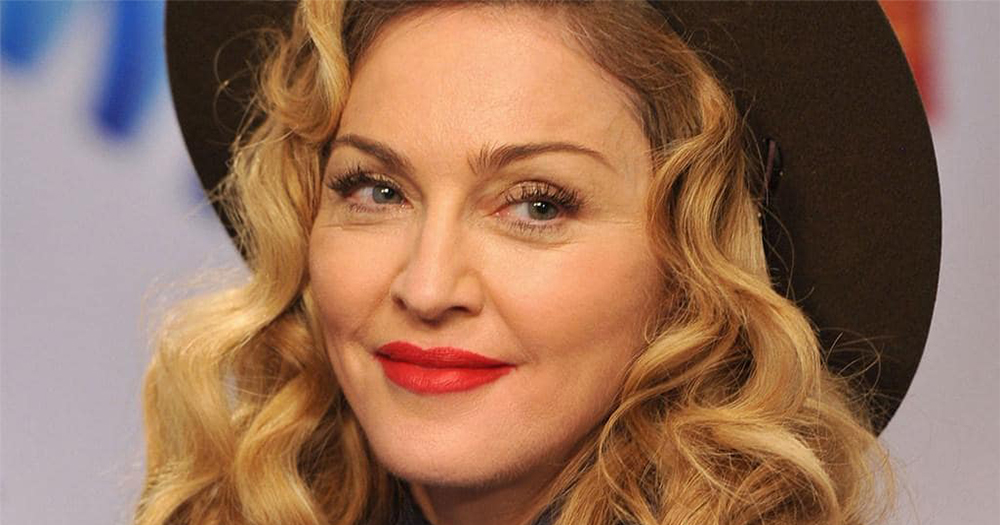 Madonna smiling in a selfie wearing a hat