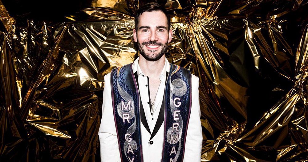 Mr Gay Europe winner Enrique Doleschy in suit and sash stands against a gold metallic background
