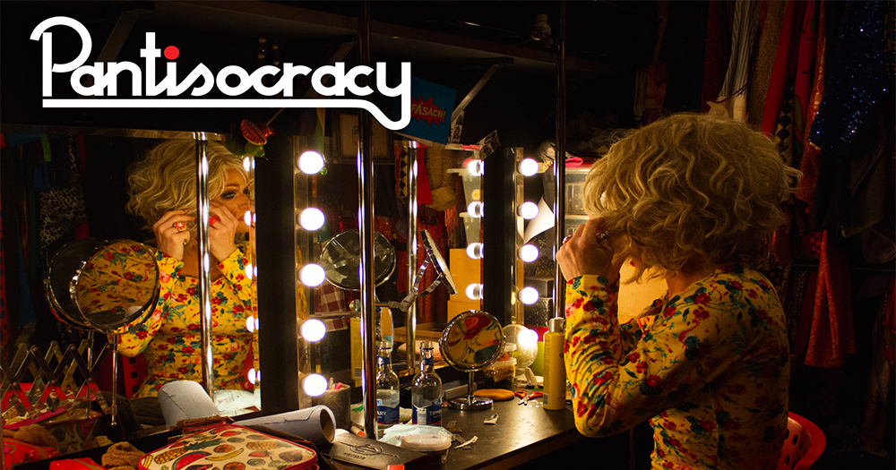 Panti, in full drag, looks at her reflection in a dressing room mirror and fixes her earring, the Pantisocracy podcast logo superimposed on the image