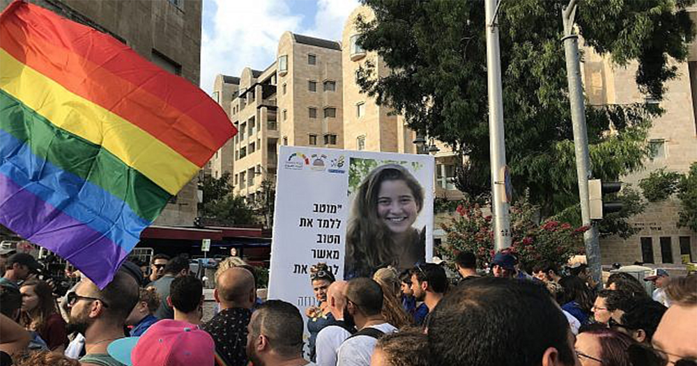 Marchers in the Jerusalem Pride Parade, some holding rainbow flags, one holding a banner with the image of a young woman murdered at the 2015 event