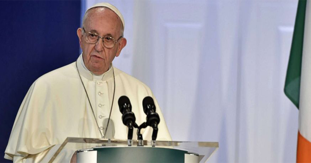 The Pope speaking into a microphone, the Irish flag by his side