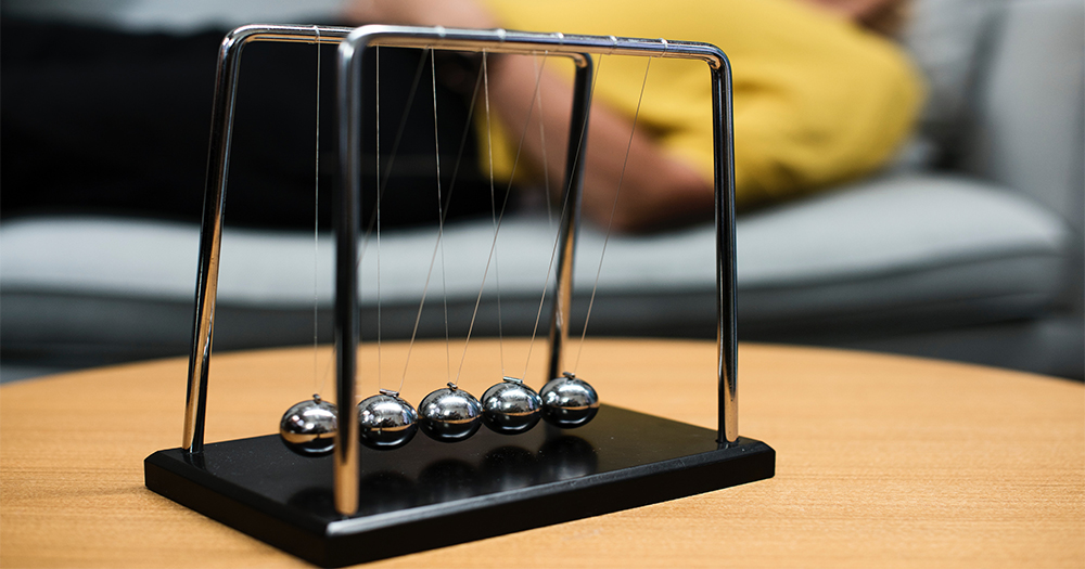 A Newtons Cradle on the desk of a psychologist, a patient reclining on the couch in the background